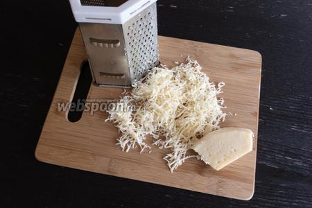 Твёрдый сыр (50 г) натереть на средней тёрке. Отправить сыр к омлету и ещё 2 минуты потушить.