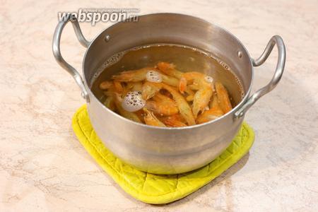 Креветки (200 г) засыпать в кипящую воду, добавить соль и специи по вкусу, варить 40 секунд.