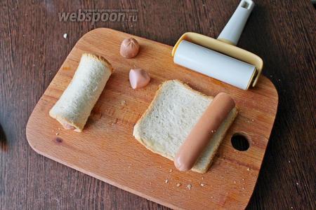 Сосиску (всего 8 шт) освободите от плёнки и выложите на край раскатанного хлеба.