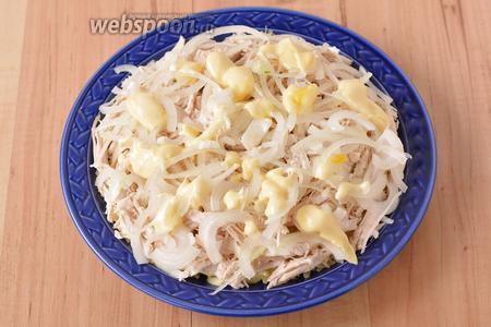 На картофель выложить подготовленное куриное филе. 35 грамм лука очистить, нарезать тонкими перьями, помять руками и равномерно выложить на куриное филе. Сверху равномерно распределить 40 грамм майонеза.