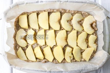Форму для выпечки застелите пергаментной бумагой, выложите тесто и разложите яблоки. Выпекайте в духовке при температуре 180°C 45 минут.