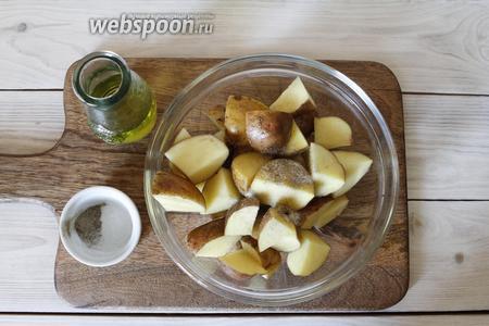Кубики картофеля переложить в глубокую чашу. Посолить (7 г) и приправить чёрным перцем (3 г). Добавить (3 ст. л.) оливкового масла. Всё хорошо перемешать.