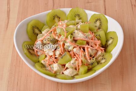 Выложить салат в салатник. 1 киви очистить, нарезать тонкими полукружками и украсить ими салат. Салат с киви и курицей готов к подаче.