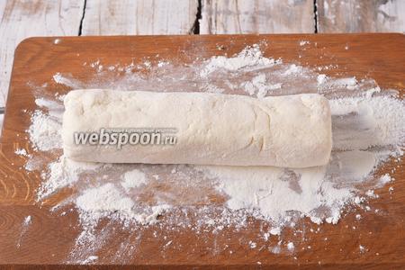 На разделочной доске распределить 2 столовые ложки муки. Выложить творожную массу на муку, в виде цилиндра, и прокатать по столу с мукой, панируя цилиндр со всех сторон.
