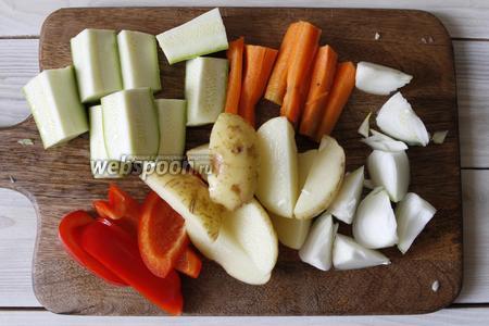 Подготовить овощи, я нарезала их крупными брусочками: картофель (4 штуки разрезать на 4 части), 1 морковь, 1 кабачок, 1 репчатый лук, 1 болгарский перец.