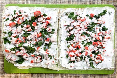 Разрежьте 1 лист лаваша на 4 части. 3 из них обмажьте тонким слоем сыра с чесноком. Посыпьте зеленью и крабовыми палочками. Наложите слои один на другой и сверху накройте четвертым листом лаваша.