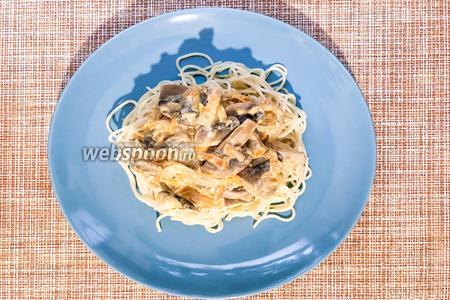 Выложите готовые спагетти на тарелку и сверху выложите сметанно-грибной соус. Приятного аппетита.