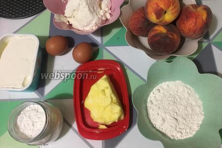 Для приготовления чизкейка с персиками, нам понадобится пшеничная мука, сливочное масло и сахар для основы, творожный сыр крем-чиз, творог, куриные яйца, сахарная пудра, свежие персики для крема. Все ингредиенты достаём заранее, примерно за 30 минут, чтобы они все стали комнатной температуры.
