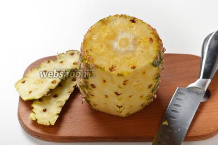 Острым ножом срезать верх и низ одного крупного ананаса, а затем очистить от кожуры.