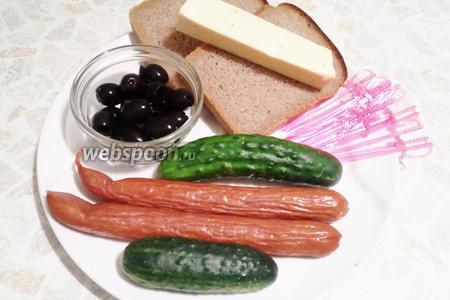 Подготовим необходимые ингредиенты: хлеб, сыр, маслины, огурцы, охотничьи колбаски.