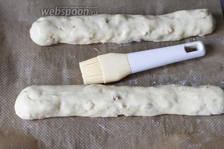 Полена выложить на пергамент для выпечки. Смазать их белком. Отправить их в заранее разогретую духовку (180°С).