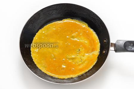 На сковороде, диаметром 18-20 см, разогреть 10 мл подсолнечного масла. Вылить желтковую смесь на сковороду и распределить её в виде тонкого блинчика.